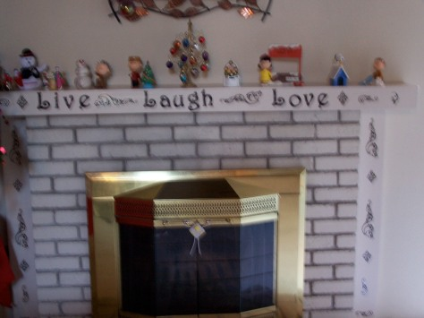 Live, laugh, love fireplace with Christmas stuff.